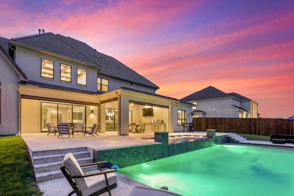 Illuminated home with pool at dusk with purple and pink sky